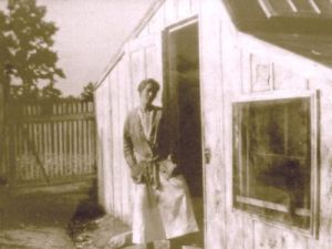 woman in front of chicken coop